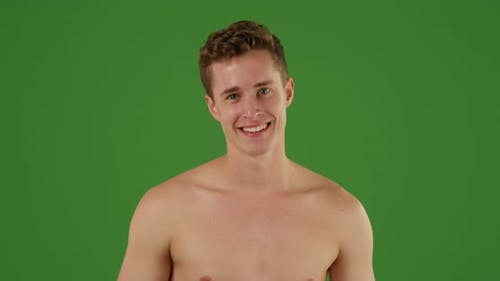 Portrait of young millennial Caucasian male with a fedora on  green screen