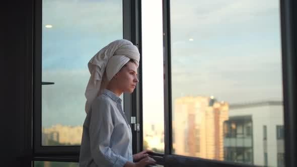 Junge Frau in einem Hemd trifft auf den Morgen auf dem Balkon, Tagesablauf
