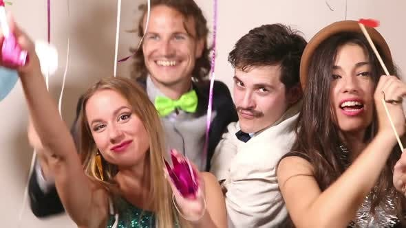 Thumbnail for Two girls and two guys playing with props in party photo booth