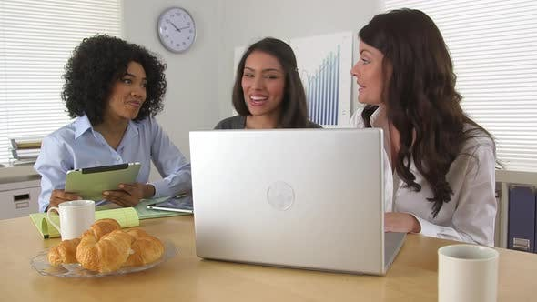 Thumbnail for Three business women celebrating at good news while using laptop computer