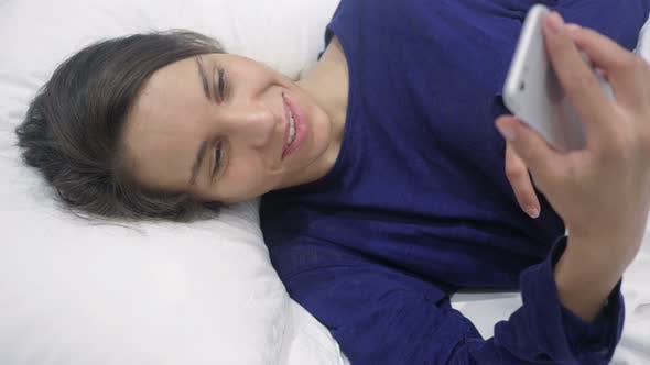 Thumbnail for Online Video Chat on Smartphone by Hispanic Woman in Bed
