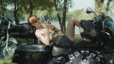 Stylish Female Biker Relaxing with Phone on Bike