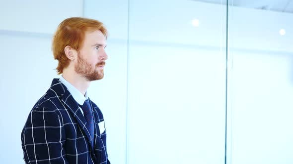 Cover Image for Side View of Pensive Redhead Businessman Looking through Office Window