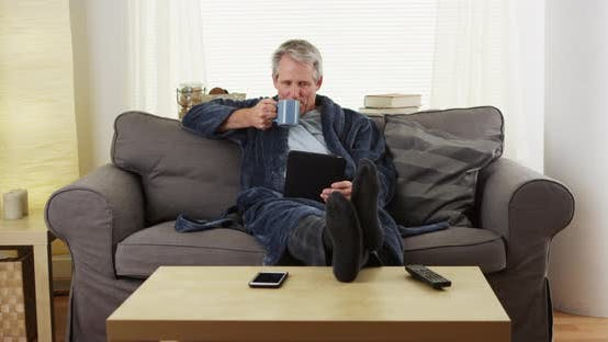 Senior man reading tablet book on couch