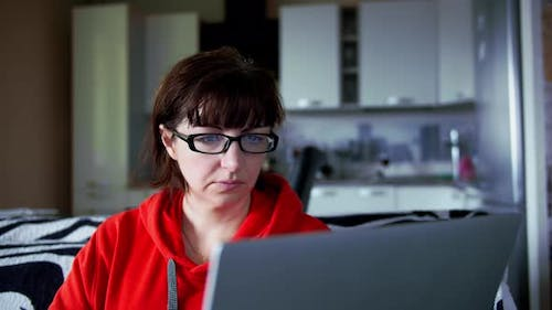 Woman Sits at Home Near a Laptop and Surfs the Internet, Reflection in Glasses