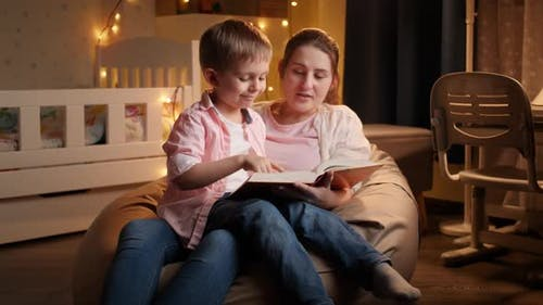 Slow Motion of Young Mother Reading Bedtime Story To Her Little Son Before Going To Sleep