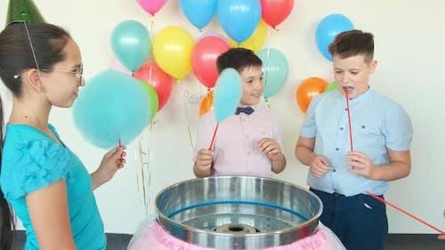 Kinder essen Baumwolle Süßigkeiten in der Nähe Maschine auf Geburtstagsparty
