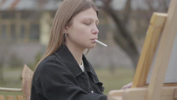Thumbnail for Portrait of Young Girl Painter Sitting in Front of Wooden Easel Drawing a Picture and Smoking