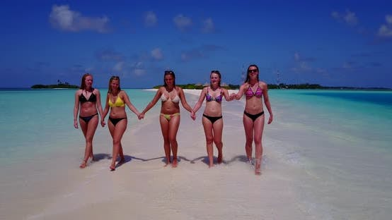 Young happy ladies on vacation enjoying life at the beach on sunny blue and white sand background 4K