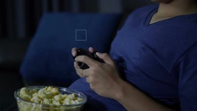 close up hand playing video game with joystick at night