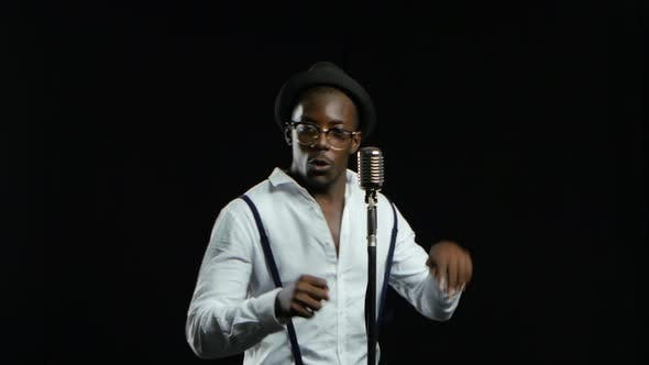 Thumbnail for Man African American Singer Sings Into a Microphone and Dance. Black Background