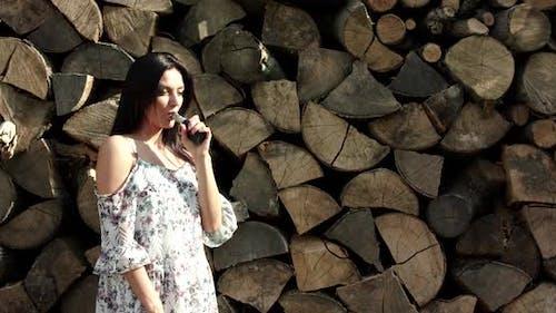 Seductive Brunette Smoking Ecigarette on Wood Background