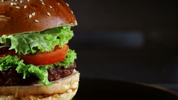 Thumbnail for Burger with cutlet rotates on a wooden Board on a black background.