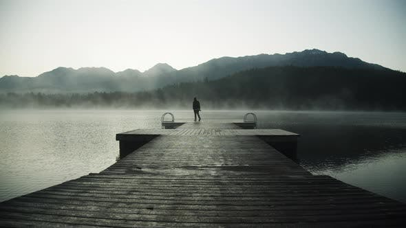 Thumbnail for Silhouette of a Man Standing at the End of a Boardwalk on a Misty River