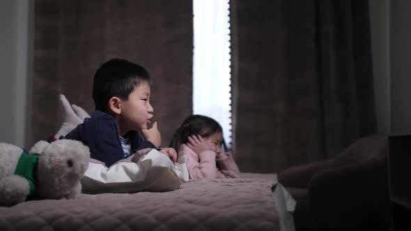 Thumbnail for Cute Chinese Siblings Watching TV Lying on Bed
