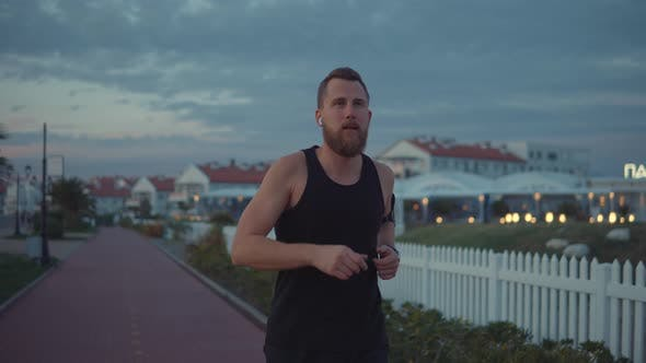 Thumbnail for Young Male Jogger Is Listening Music During Evening Running Outdoors