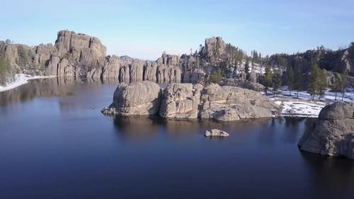 Aerial Drone Going Up of Lake or Pond and Forest and Rocks Granite Water Impoundment in Black Hills