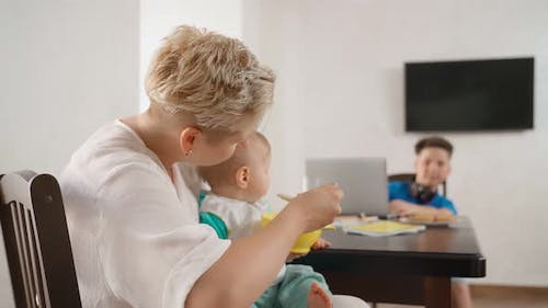 Mother Spoon Feeding Baby Boy While Teenager Using Laptop