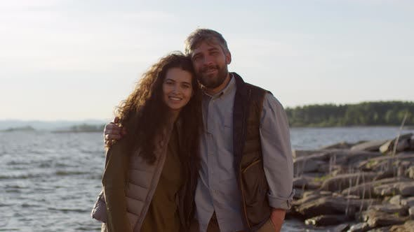 Thumbnail for Portrait of Happy Tourist Couple Standing on Lakeshore at Sunset