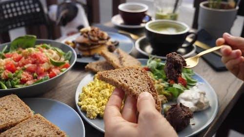 Hands Spreading Dips on Piece of Brown bread.Healthy Balanced Vegan Brunch.
