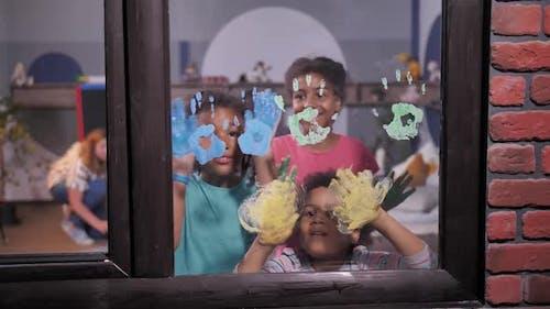 Mulatto Girls Making Handprints on Window Glass