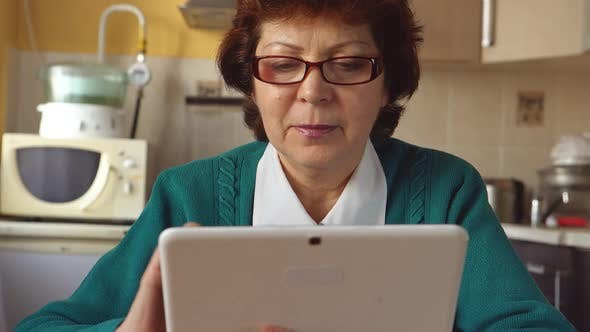 Thumbnail for Portrait Of A Mature Woman With A Glasses Is Using A Tablet Pc At Home