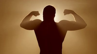 Man showing muscles in the spotlight