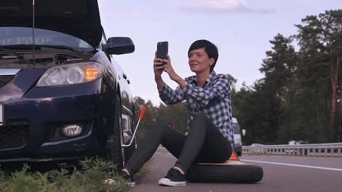 Caucasian weiblich versuchen, einen Reifen im Freien zu ändern