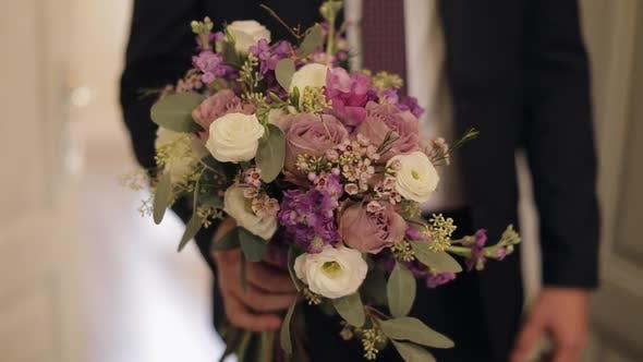 Thumbnail for Bräutigam mit Hochzeitsstrauß in seinen Händen. Weißes Hemd, Jacke