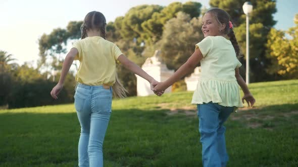 Little Girls Running in a Hedge Maze Two Sisters Kids Hold Hands and Run in Big Green Labyrinth in