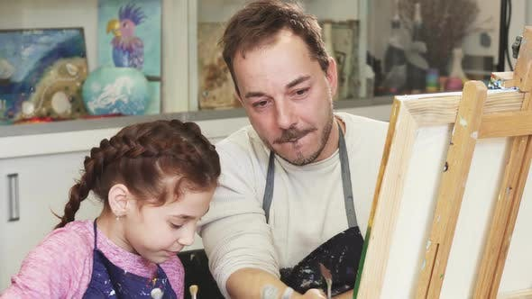 Thumbnail for Happy Little Girl Painting a Picture with Her Father