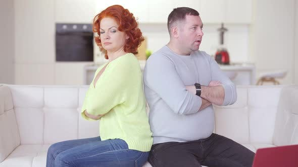 Argued Adult Couple Sitting Back to Back on Couch Thinking