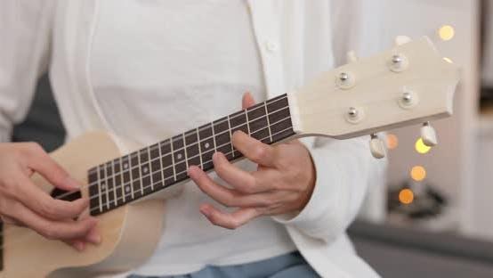 Thumbnail for Woman play ukulele at home