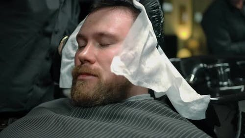 A Barbershop Client is Wiped Dry with a Special Towel