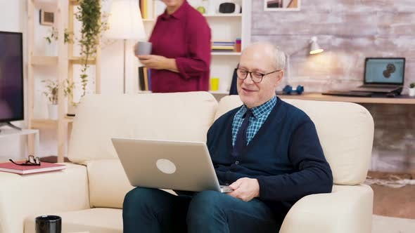 Elderly Age Couple with Glasses Sitting on Sofa During a Video Call on Laptop.