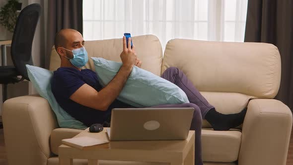 Thumbnail for Man with Protective Mask Laying on Sofa