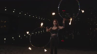 Firegirl Performing Art of Twisting Hoops at Dusk