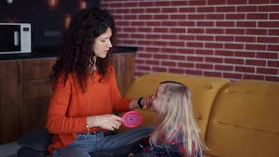 Mom is Combing the Hair for the Daughter in the Living Room