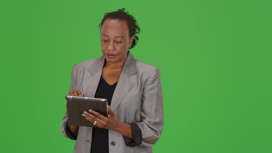 Thumbnail for A black businesswoman using a tablet computer on green screen