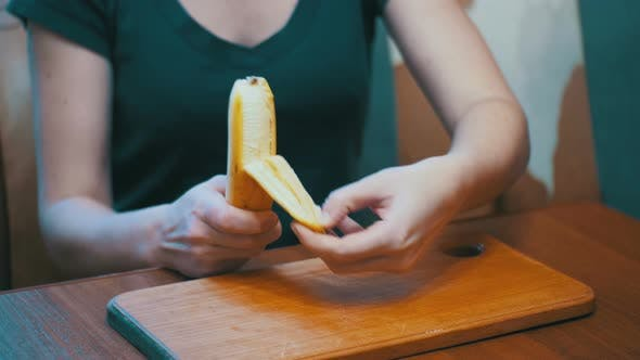 Cover Image for Woman Cleaning a Banana While Sitting at a Table in a Home Kitchen