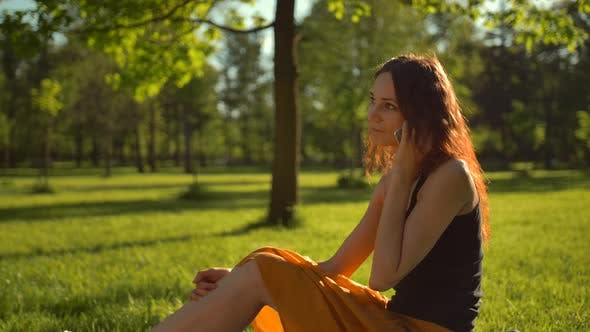 Thumbnail for Happy Attractive Sexy Lady Sitting on Green Grass and Have Conversation Via Digital Phone.