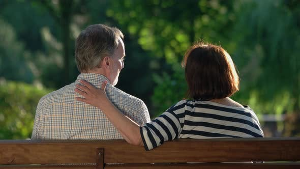Rear View of Romantic Elderly Couple Sitting on Bench at Park