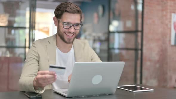 Successful Online Payment on Laptop By Young Man