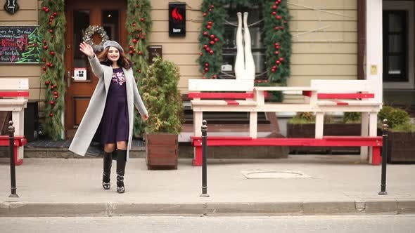 Thumbnail for Beautiful Girl in Grey Coat and Beret Walking Towards Christmas Shops.