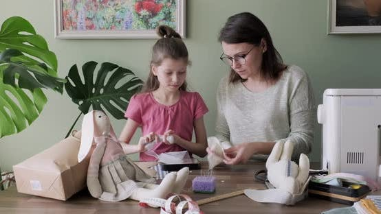 Thumbnail for Mother and Daughter Child Together Sewing Toy Hare Doll, Hobbies and Leisure at Home