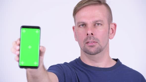 Thumbnail for Portrait of Happy Blonde Man Smiling While Showing Phone
