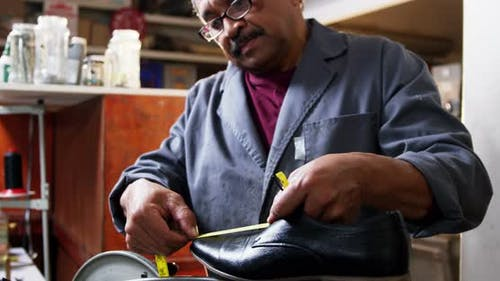 Shoemaker measuring a shoe with measure tape