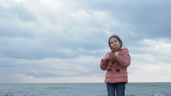 Thumbnail for Little Girl Hugs a Teddy Bear on the Beach