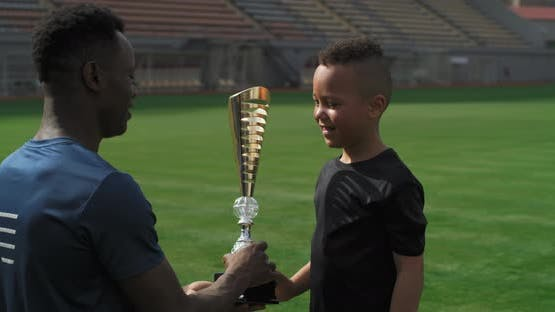 Cheerful Boy Taking Trophy From Black Trainer