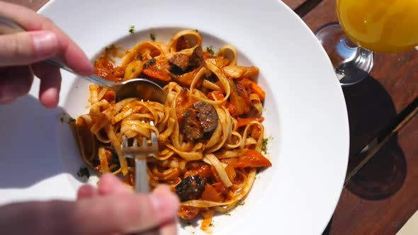 Thumbnail for Closeup Of Eating Vegetable Vegan Pasta In Tomato Sauce With A Fork And Spoon